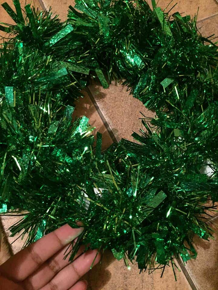 Paper plate wrapped in green tinsel DIY Christmas Wreath