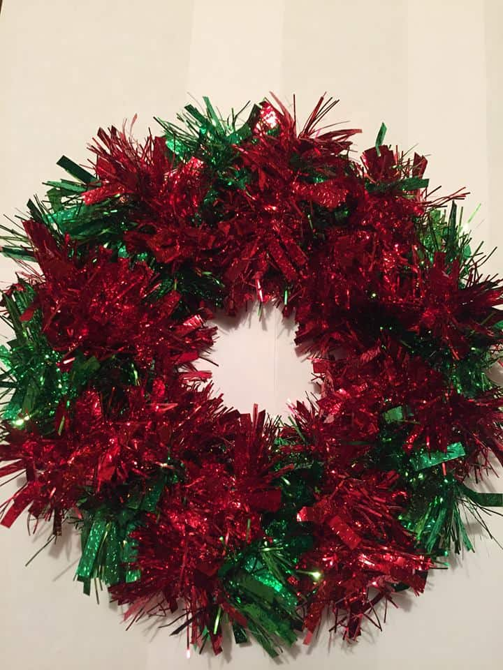 Paper plate wrapped in alternating bands of red and green tinsel DIY Christmas Wreath