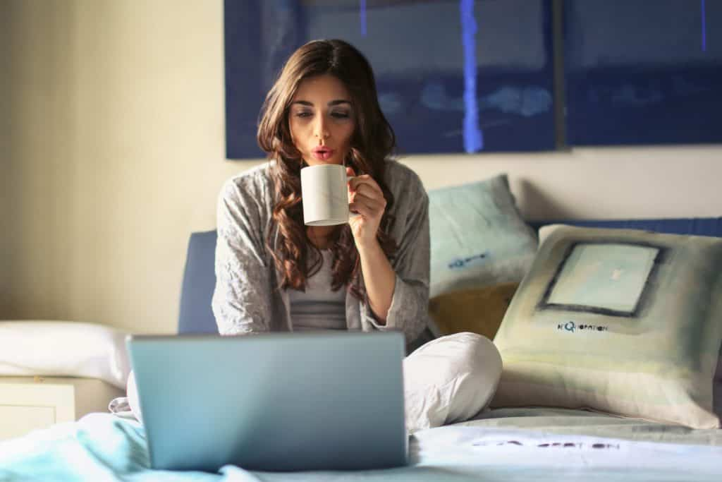 woman drinking coffee and working on laptop on bed - best transcription companies that hire beginners