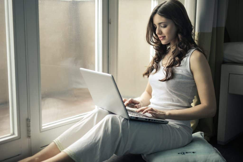 woman working on laptop by large window - best transcription companies that hire beginners