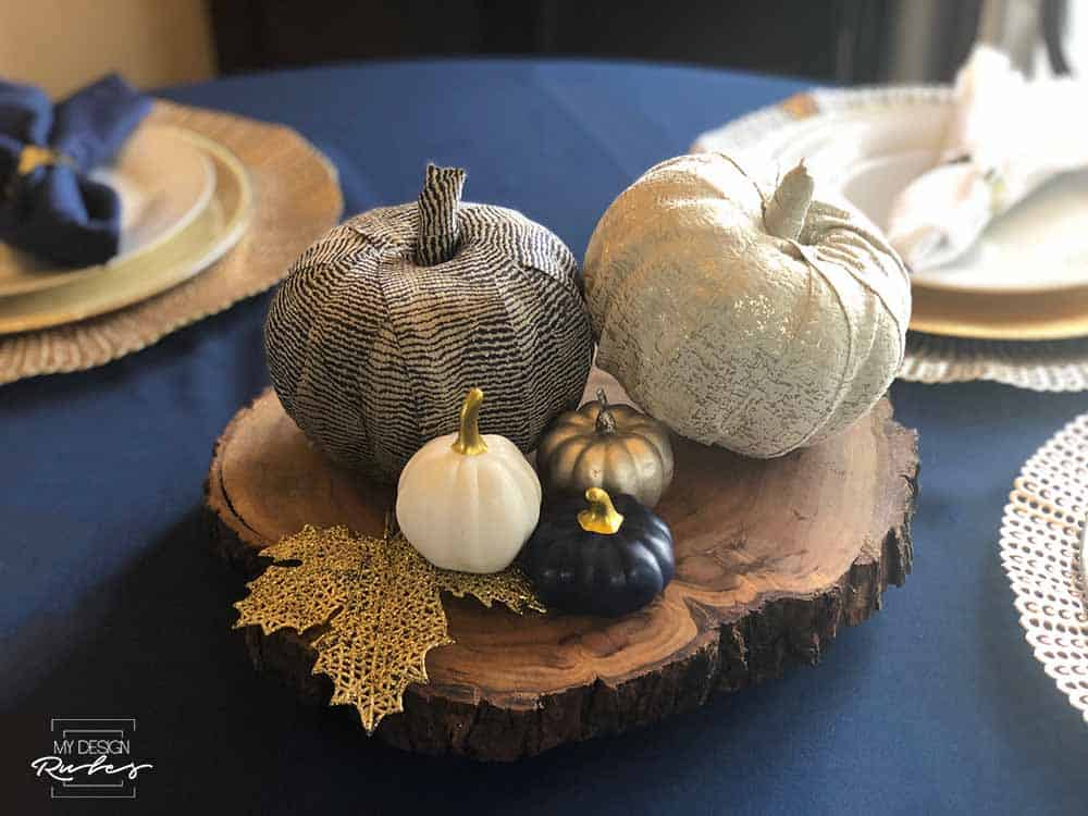 cloth decorated pumpkins on wood block on table