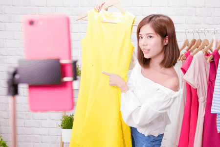 woman holding up yellow dress to take pic to sell on offerup